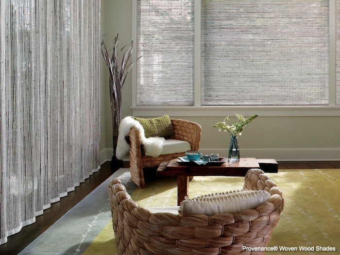 A living room with woven wood shades and a silky rug.
